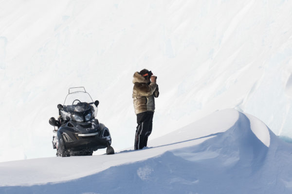 Snowmobile and guide scouting landscape in the arctic
