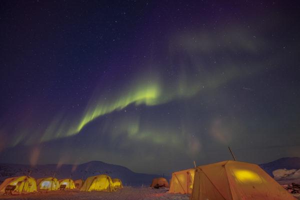 Heated tents below aurora borealis