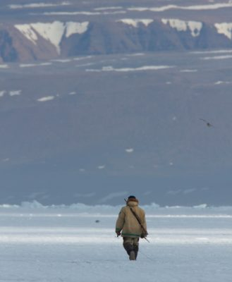 Inuit walking in the arctic