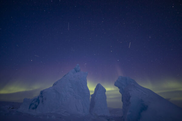 northern lights above white icebergs