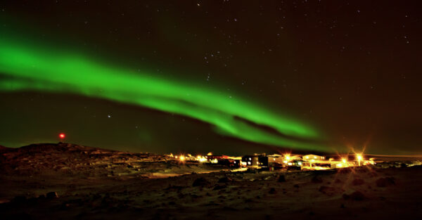 northern lights above city lights in the arctic